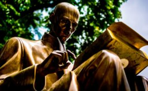 statue of man reading book
